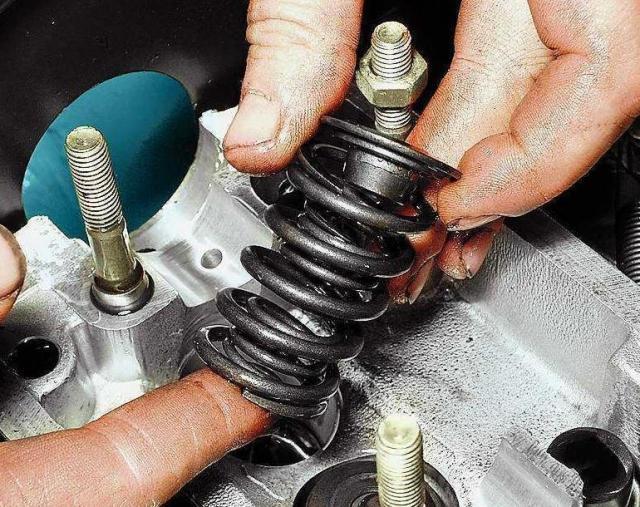 Выньте верхнюю тарелку пружин, внутреннюю и наружную пружины клапана.