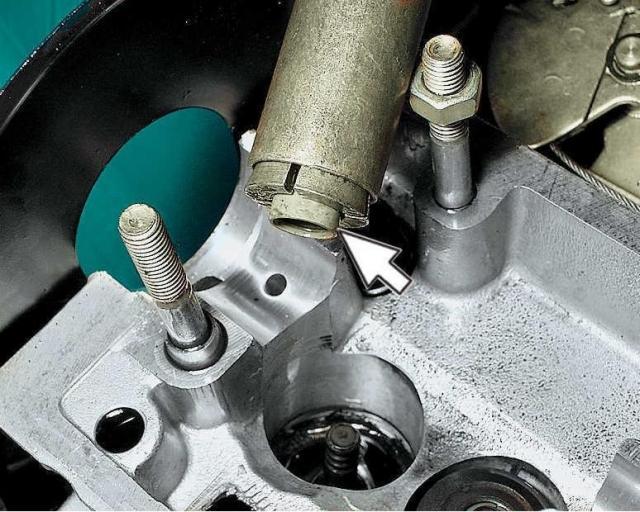 Выньте колпачок из цанги приспособления. При отсутствии приспособления для снятия колпачков используйте пассатижи. При этом усилие нужно прикладывать строго вверх и не проворачивать колпачки, чтобы не повредить направляющие втулки клапанов.