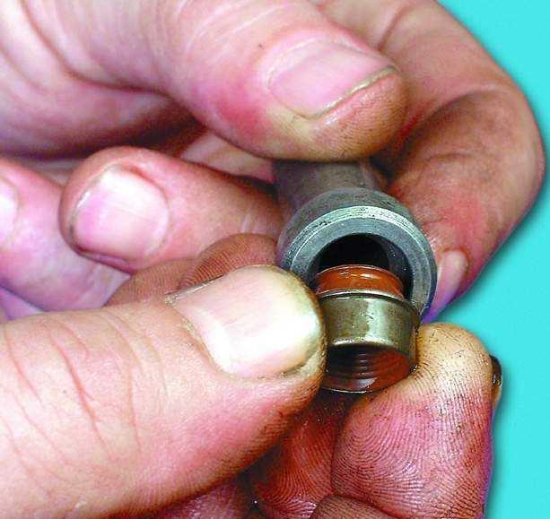Окуните маслосъемный колпачок в моторное масло и вставьте его в оправку.