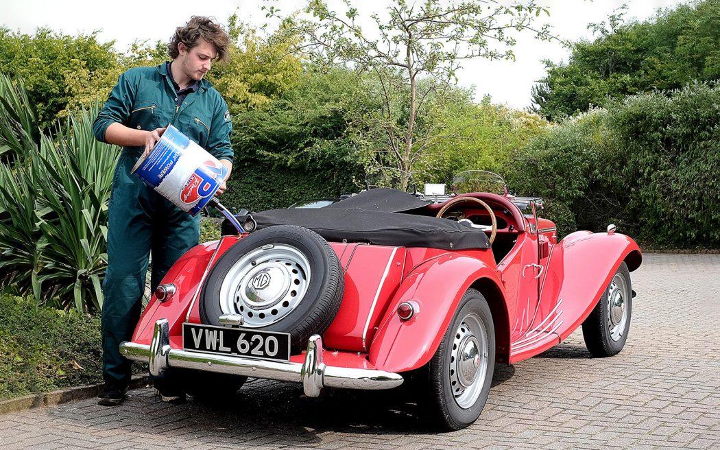 Водитель классического родстера MG заправляет бак со стороны обочины (своей, британской).
